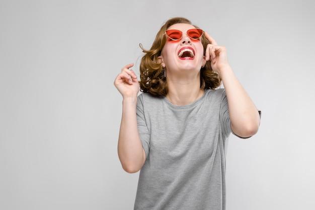 Ragazza affascinante in una maglietta grigia. ragazza felice con gli occhiali rossi. la ragazza ride