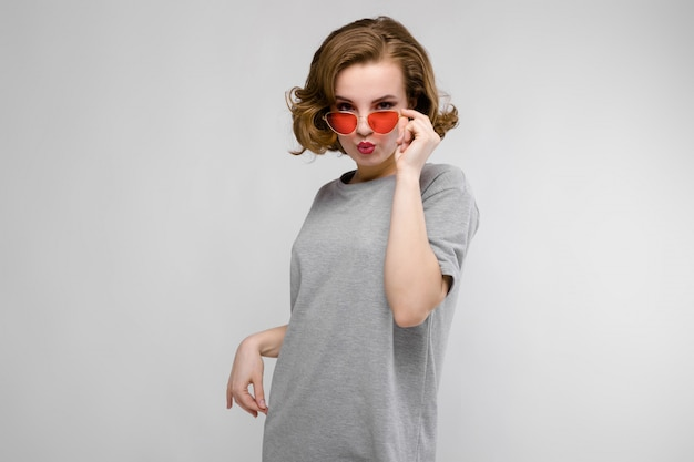 Ragazza affascinante in una maglietta grigia. ragazza felice con gli occhiali rossi