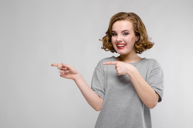Ragazza affascinante in una maglietta grigia su un fondo grigio. la ragazza indica con le dita di lato