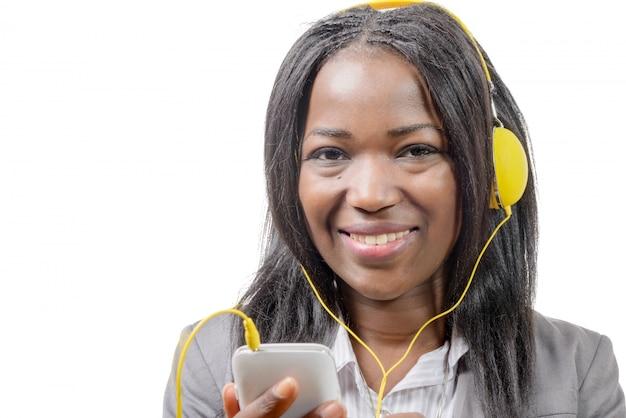Ragazza africana affascinante allegra che tiene telefono cellulare e che ascolta la musica