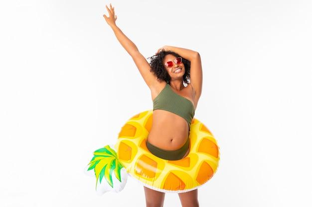 Ragazza africana attraente in costume da bagno verde e vetri con l'ananas del cerchio di nuoto sulla parete bianca