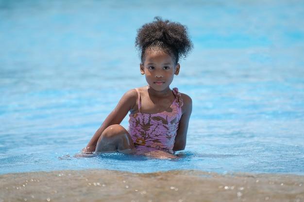 Ragazza africana che si siede e che gioca acqua nella piscina al parco di divertimenti.