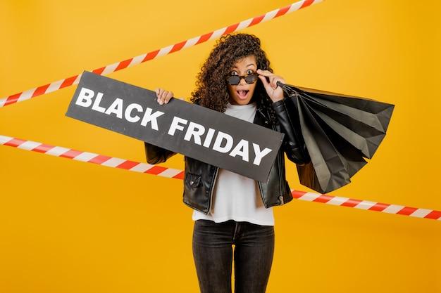 Ragazza africana emozionante con i sacchetti della spesa neri del segno e della carta di venerdì isolati sopra giallo con nastro adesivo