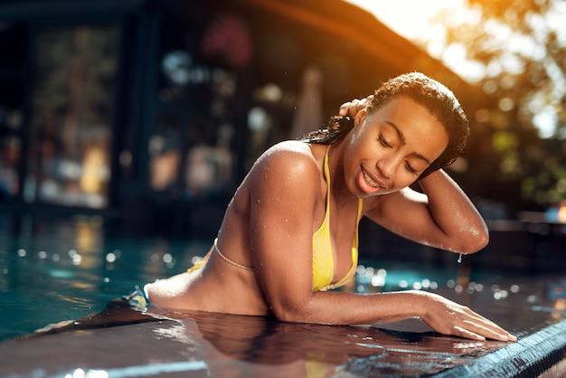 Ragazza africana in bikini godendo giornata di sole a bordo piscina.