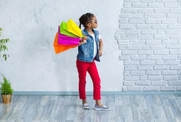 Ragazza afro felice con i sacchetti della spesa