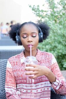 Ragazza afro nera in abito etnico con le cuffie e gli occhi chiusi, seduto in un caffè all'aperto, ascoltando musica e bevendo cocktail di latte