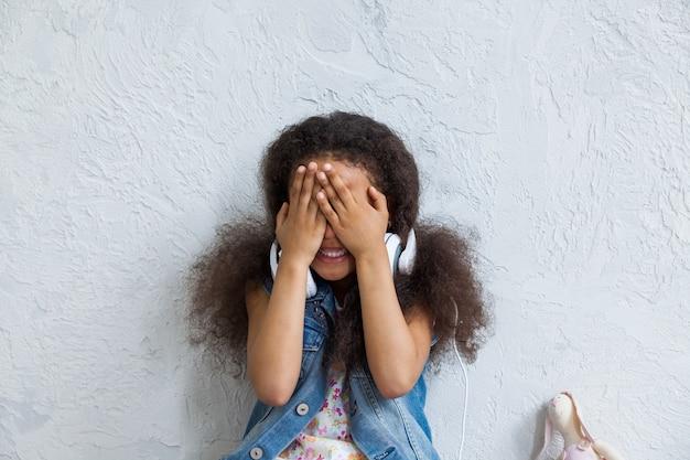 Ragazza afro sveglia a casa che ascolta la musica