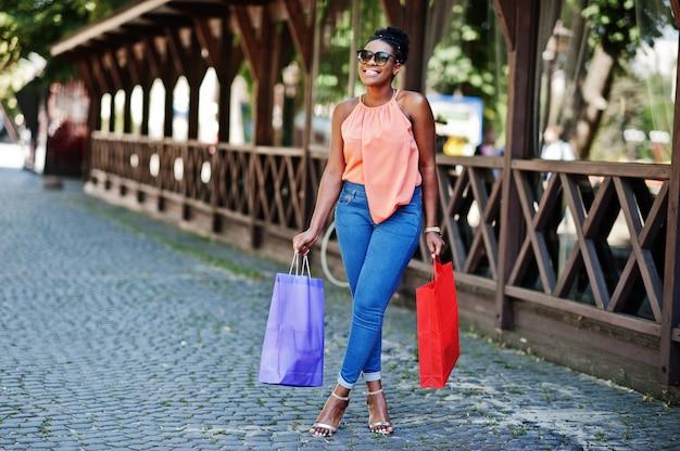 Ragazza afroamericana casuale con la camminata colorata dei sacchetti della spesa all'aperto. acquisto alla moda della donna di colore.