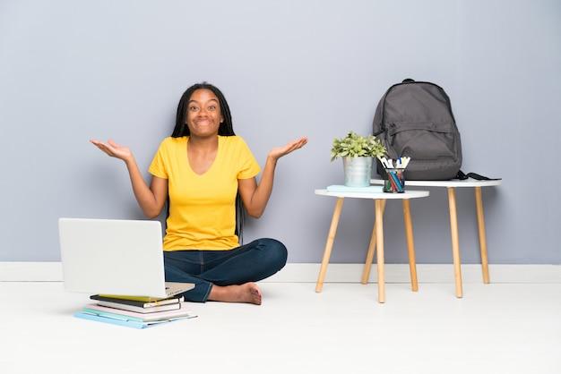 Ragazza afroamericana dello studente dell'adolescente con capelli intrecciati lunghi che si siedono sul pavimento che ha dubbi con l'espressione confusa del fronte