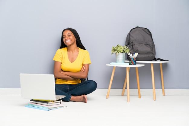 Ragazza afroamericana dello studente dell'adolescente con capelli intrecciati lunghi che si siedono sulla risata del pavimento