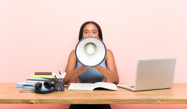 Ragazza afroamericana dello studente dell'adolescente con capelli intrecciati lunghi nel suo posto di lavoro che grida tramite un megafono
