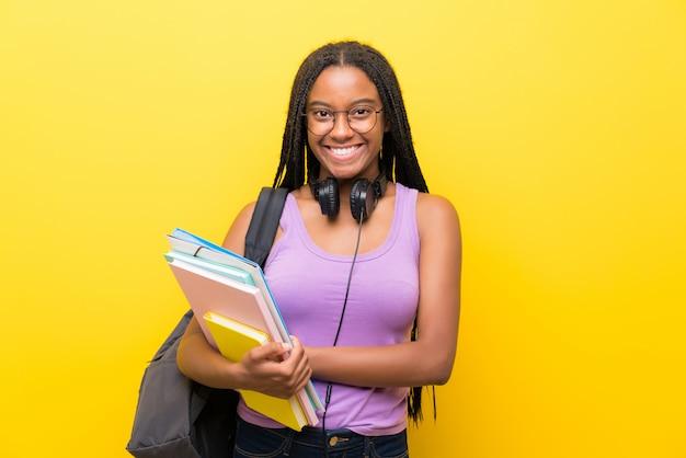 Ragazza afroamericana dello studente dell'adolescente con capelli intrecciati lunghi sopra la risata gialla della parete