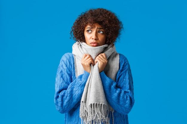 Ragazza afroamericana sciocca e triste, cupa che guarda fuori inverno ventoso, nevoso, collo avvolgente con sciarpa calda, tremore da sensazione di freddo disagio da bassa temperatura a casa, blu