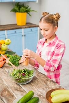 Ragazza aggiungendo il pepe nella ciotola di insalata fresca sul tavolo di legno