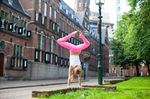 Ragazza al mattino facendo yoga in città