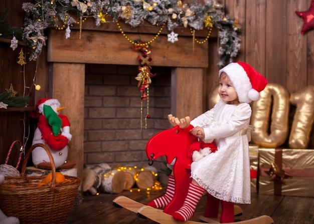Ragazza all'albero di natale con il giocattolo dei regali. l'interno è decorato con stelle, palline e ghirlanda. il camino è vestito con abiti natalizi. the shine of the numbers, 2019