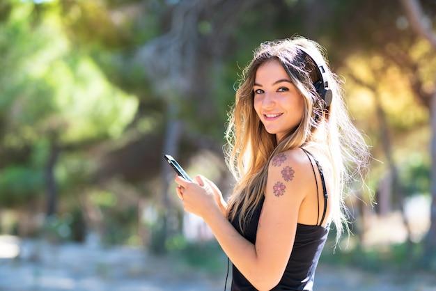 Ragazza all'aperto in un parco che ascolta la musica con il cellulare