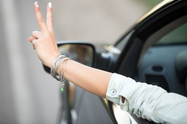 Ragazza alla guida e mostrando il gesto di vittoria