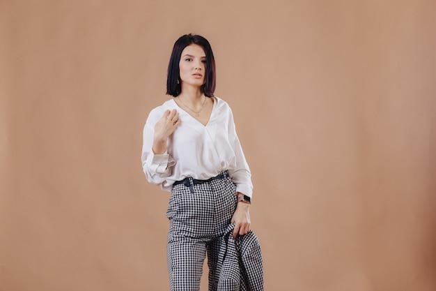 Ragazza alla moda attraente in abbigliamento di affari che posa sul fondo crema. concetto di abiti eleganti e raffinatezza.