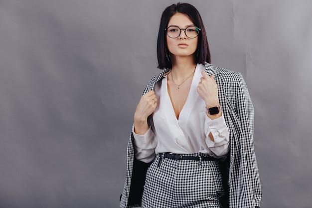 Ragazza alla moda attraente in vestiti di affari che posano sulla parete scura. concetto di abiti eleganti e raffinatezza.