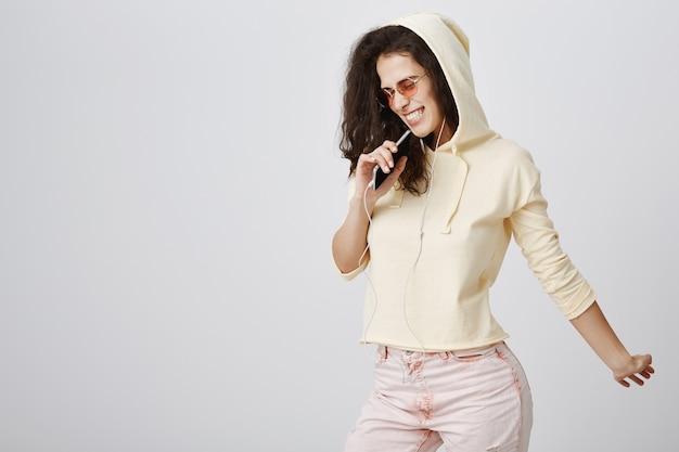 Ragazza alla moda che gioca l'app karaoke, canta canzoni nel telefono cellulare, indossa gli auricolari