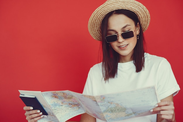 Ragazza alla moda che posa con l'attrezzatura di viaggio su una parete rossa