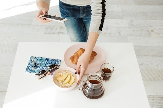 Ragazza alla moda che prende le immagini con la mela, taccuino sulla tavola bianca.