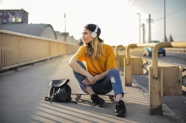 Ragazza alla moda che si siede su uno skateboard