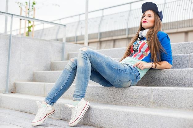 Ragazza alla moda che si siede sui gradini