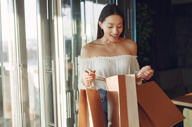 Ragazza alla moda che sta in un caffè con i sacchetti della spesa