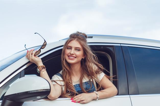 Ragazza alla moda che viaggiano in auto