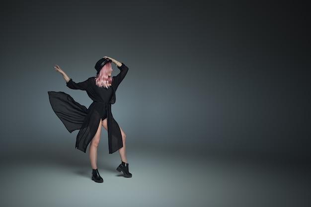 Ragazza alla moda con i capelli rosa, che indossa abito nero volante