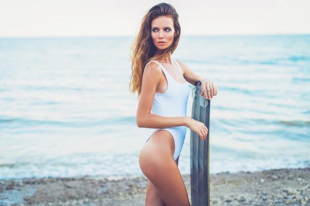 Ragazza alla moda con il bordo che sta sulla spiaggia
