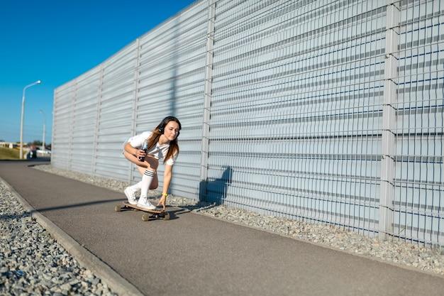 Ragazza alla moda in calze bianche cavalca sul longboard per strada e ascolto musica.