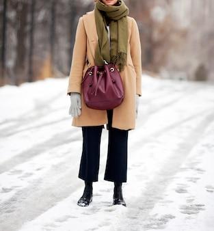 Ragazza alla moda in cappotto beige con sciarpa e borsa
