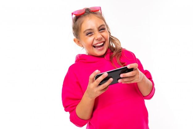 Ragazza alla moda in felpa rosa, occhiali da sole rosa è felice e sorride, comunica con gli amici o la famiglia isolata sulla superficie bianca