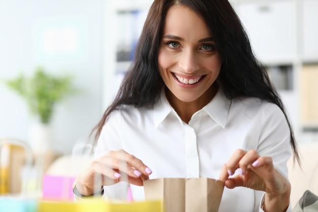 Ragazza alla moda in ufficio e gode del pacchetto