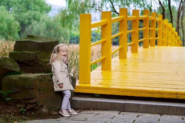 Ragazza alla moda llittle su un ponte giallo nel parco