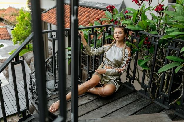 Ragazza alla moda nello sguardo alla moda con due trecce lunghe che si siedono sulle scale di legno vicino alla sua casa