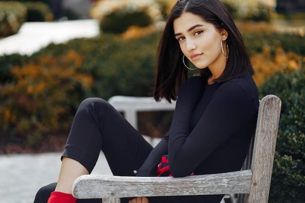 Ragazza alla moda, seduto su una panchina a scuola