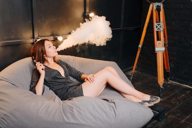 Ragazza alla moda splendida che fuma una sigaretta elettronica - dispositivo d'avanguardia esente da tabacco, espirando vapore durante il riposo e relax sul pouf grigio nella vecchia stanza buia. in casa