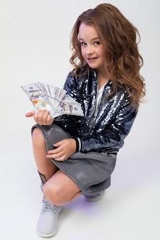 Ragazza alla moda sveglia che tiene un mucchio di soldi con un fan mentre sedendosi sul pavimento dello studio