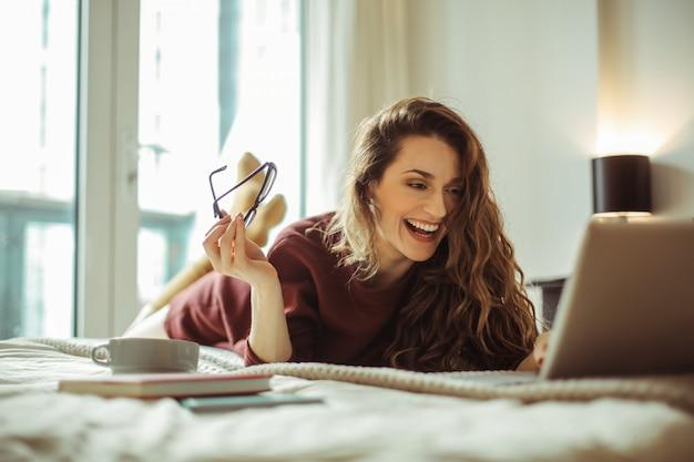 Ragazza allegra che ride durante una videochiamata con un suo amico