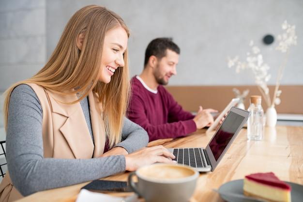 Ragazza allegra con i capelli lunghi guardando la sua amica con un sorriso mentre comunica tramite chat video dal laptop