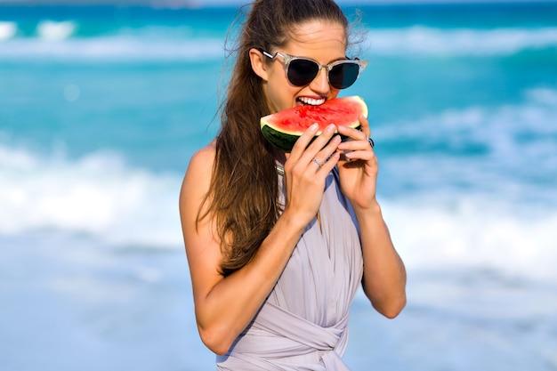 Ragazza allegra con lunghi capelli castano chiaro che morde un'anguria. ritratto del primo piano del modello femminile eccitato in grandi occhiali da sole scuri che godono del cibo preferito con il sorriso.