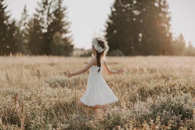 Ragazza allegra felice in un vestito bianco e con una corona di fiori sulla sua testa nel campo di estate