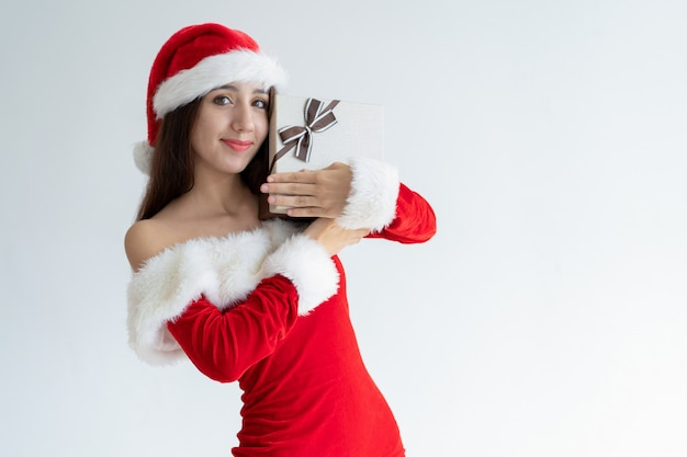 Ragazza allegra in cappello della santa felice di ricevere il regalo di natale