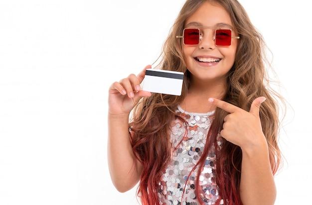 Ragazza allegra in occhiali da sole rossi quadrati che tengono la carta assegni di plastica e che indicano ad esso isolata