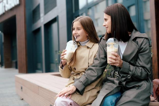 Ragazza allegra in trench sorseggiando un cocktail divertendosi con sua madre e chiacchierando in ambiente urbano