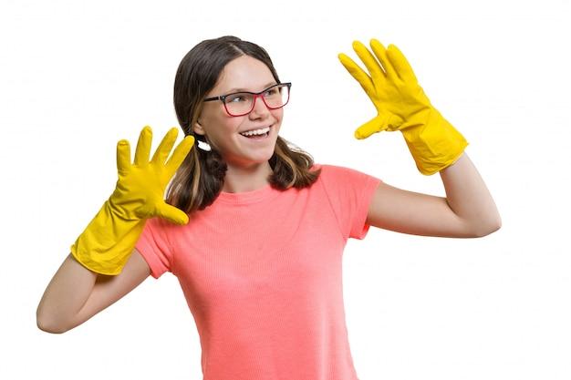 Ragazza allegra sorridente dei giovani in guanti protettivi di gomma gialli